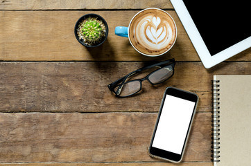 Office desk table with tablet, coffee cup ,smartphone and notebook.Top view with copy space