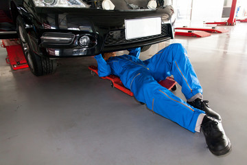 Mechanic in blue uniform lying down and working under car at the
