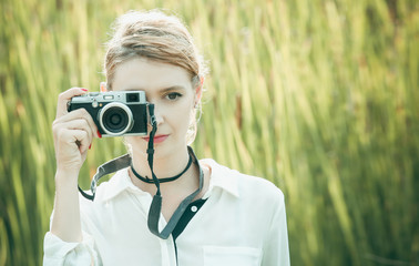 Outdoor portrait of pretty young girl with retro vintage camera