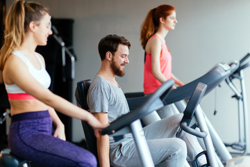 People traning in gym on various machines