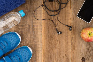 Flat lay shot of Sport equipment. Sneakers, water, earphones and