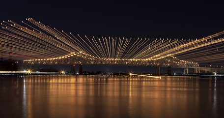 Abstract of the Crescent City Connection (twin cantilever style bridges) which goes over levee (levy) and the Mississippi River in New Orleans, Louisiana, at night, Photo Zoom Effect
