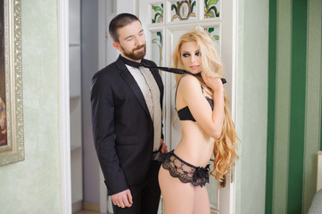 Portrait of young beautiful couple. Relationship concept. Sexy girl with long curly hair is wearing black lace lingerie, lady pulling the guy by his tie. Unshaved handsome man is wearing black suit
