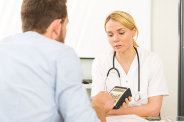 Patient paying the doctor by credit card