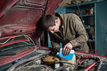 Mechanic man worker pouring antifreeze from small bottle in the cooling system during car repair works in auto service center