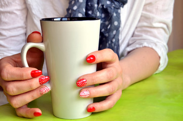 Girl with red nails on her fingers hold white cup, closeup