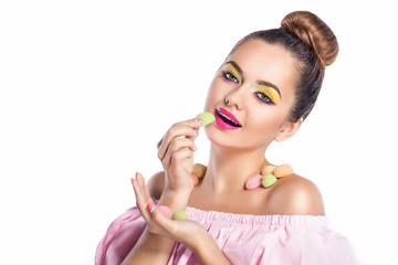 Beauty fashion model girl with colorful makeup with sweets. Diet,dieting concept. Sweets. Colorful background