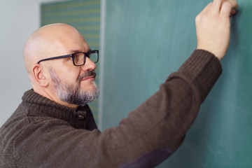 älterer lehrer schreibt an die tafel