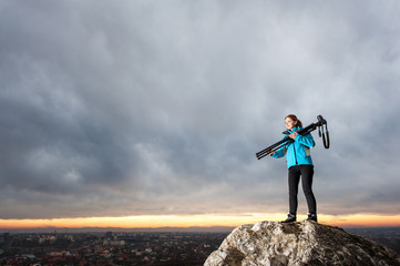 Young attractive female photographer is standing with her camera on tripod on the big rock at city overview point at the sunset. Woman is holding tripod on her shoulder