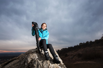 Portrait of happy woman photographer sitting on the big rock with her camera on tripod against blue evening sky. Woman is smiling and looking to the camera