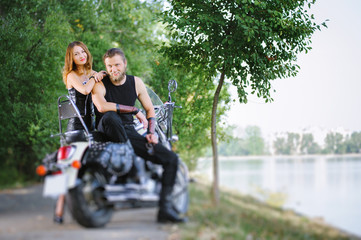 Portrait of attractive couple bikers standing by a cruiser motorbike near the lake on summer day. Tilt shift lens blur effect.