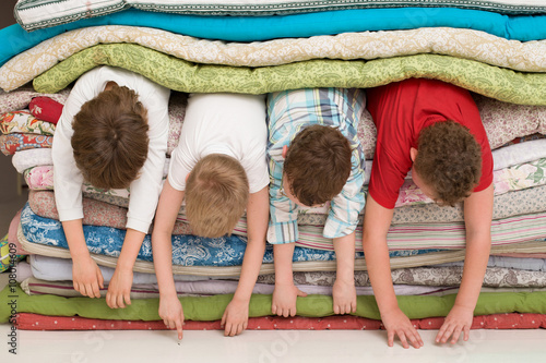 pile of mattresses. kids laying inside the pile of mattresses and having fun. slumber party. funny activities r