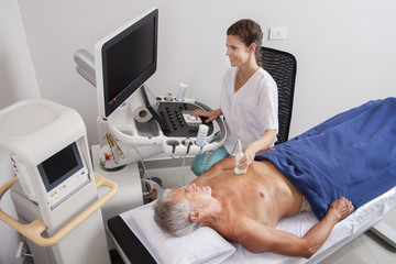 Woman doctor analyzing patient with ultrasound
