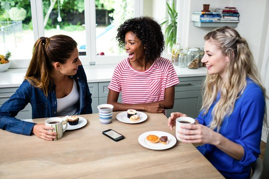 Female friends laughing while having breakfast