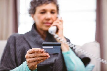 Mature woman holding credit card while talking on telephone