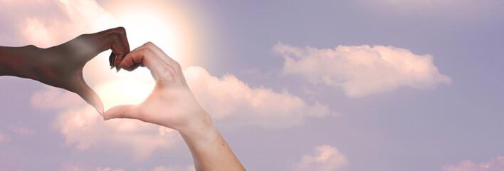 Schwarze und weiße Hand bilden ein Herz vor blauem Himmel