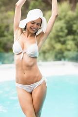 Woman in bikini standing by swimming pool