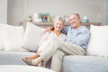 Portrait of romantic senior couple sitting on sofa in living room at home