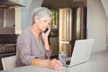 Serious senior woman talking on mobile phone