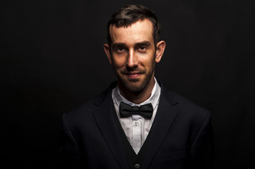 Fashionable man in siute and bow tie over dark background.