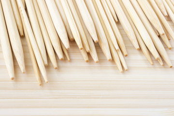 Various bamboo wooden knitting needles on wooden background.