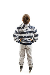 Back view young boy on rollers looking at wall. Rear view. Isolated on white background
