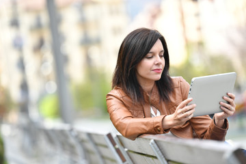 Dark-haired woman sitting on bench with tablet