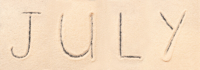 July lettering drawn on sand