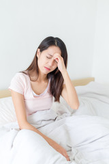Woman feeling dizzy and sitting on bed