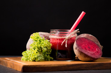 Fresh beetroot smoothie in the glass on black stone. Lifestyle concept