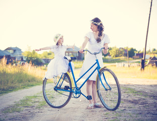 Beautiful mother and daughter traveling on a bicycle.