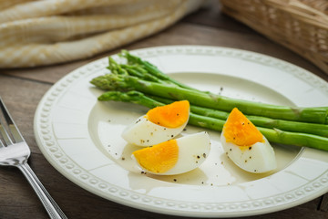 Boiled egg with asparagus on plate
