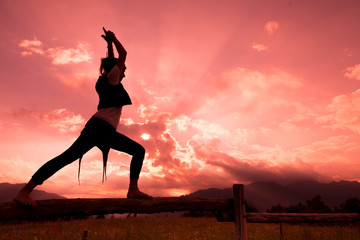 Girl on fence in nature with red sky makes gymnastics yoga movem