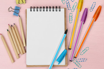 Office set with notebook, colored pens and pencils on pink background