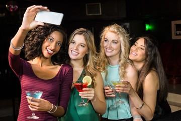 Happy friends taking a selfie in a bar