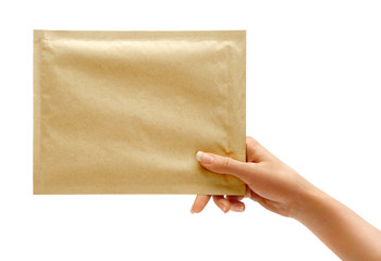Woman's hand is giving envelope. Studio photography of woman's hand holding yellow envelope