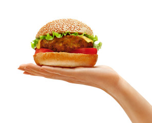 Woman's hand holding tasty hamburger isolated on a white background. Close up