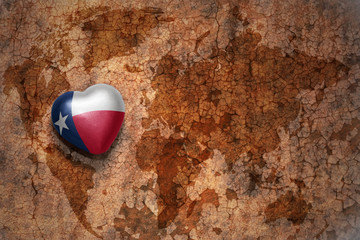 heart with texas state flag  on a vintage world map crack paper background
