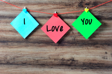 I love you on colorful paper with clothespin hanging on a string with wooden background