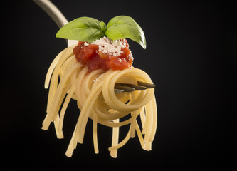 fork with spaghetti and tomato sauce isolated on black background