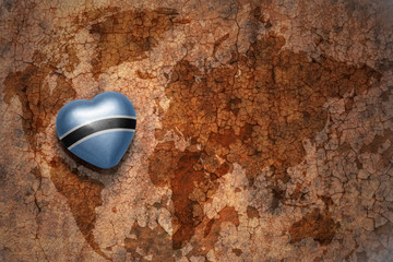 heart with national flag of botswana on a vintage world map crack paper background.