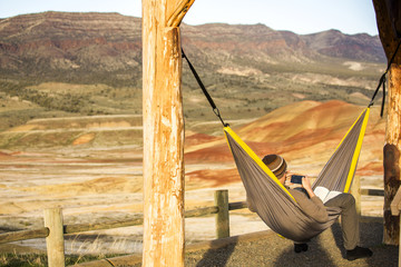 Caucasian man drinking coffee in hammock, Painted Hills, Oregon, United States