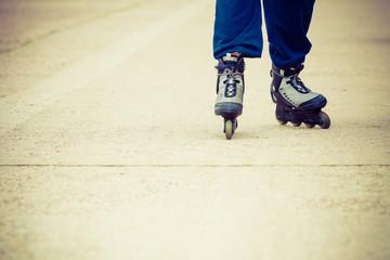 Human legs rollerblading wearing sportswear.