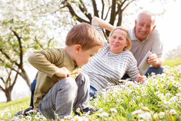 Grandparents with grandson enjoying the sunny spring day outdoors.