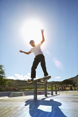Mixed race man performing trick in skate park