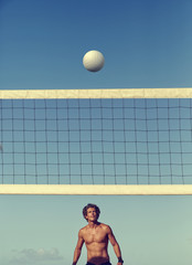 Caucasian man playing volleyball under blue sky
