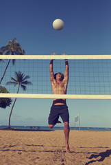 Caucasian man playing volleyball on beach