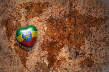 heart with national flag of ethiopia on a vintage world map crack paper background.