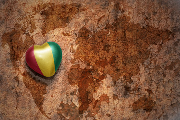 heart with national flag of guinea on a vintage world map crack paper background.