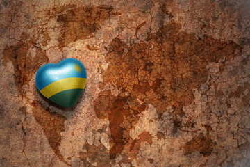 heart with national flag of rwanda on a vintage world map crack paper background.
